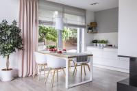 Jedálenský stôl a plastové stoličky v modernej bielej kuchyni