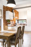 Rustikálny jedálenský stôl v kuchyni s tehlovou stenou