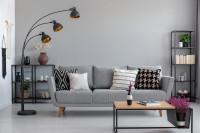 Pohovka s čiernobielymi vankúšmi v sivej obývačke