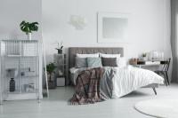 Čalúnená manželská posteľ a kovový regál vo svetlej spálni