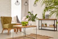 Zelené kreslo a kovové doplnky vo svetlej obývačke