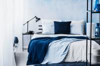 Manželská posteľ s modrou dekou a kovovými doplnkami