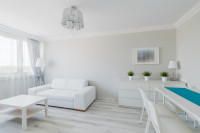 Komoda a pohovka v modernej obývačke v bielych tónoch