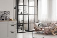Pohovka a okrúhly stolík v otvorenej obývačke s kuchyňou