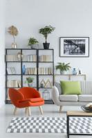 Oranžové kreslo a biela pohovka v škandinávskej obývačke