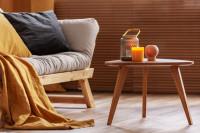 Svetlá pohovka s dekou a sviečky na drevenom stolíku