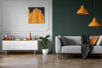 Svetlá látková pohovka v retro obývačke s oranžovými doplnkami