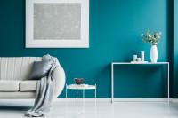 Svetlá pohovka a biele doplnky v kontraste s modrou stenou