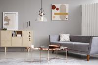 Sivá pohovka a medené stolíky v retro obývačke