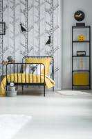 Čierna kovová posteľ a regál so žltými doplnkami