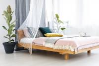Veľký drevená posteľ s dekoračnými dekami a závesmi