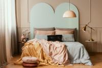 Manželská posteľ s dekoračnými vankúšmi a kovovými odkladacími stolíkmi