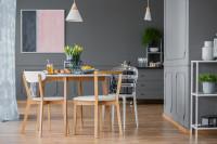 Jedálenský stôl a stoličky zo svetlého dreva v sivej jedálni