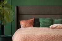 Čalúnená manželská posteľ v spálni so zelenou stenou