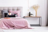 Čalúnená manželská posteľ s ružovými obliečkami a kovový odkladací stolík