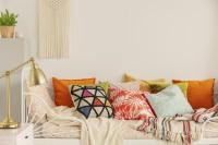 Biela kovová posteľ s pestrofarebnými vankúšmi