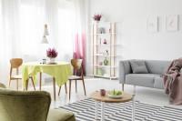 Sivá pohovka a okrúhly jedálenský stôl s drevenými stoličkami vo vzdušnej obývačke