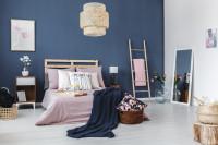 Drevená manželská posteľ v spálni s tmavomodrou stenou