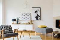 Sivé kreslo biela nízka komoda vo svetlej škandinávskej obývačke