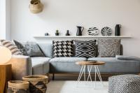 Rohová sedačka a čiernobiele dekoračné vankúše v škandinávskej obývačke