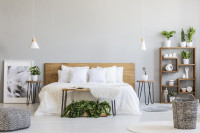 Manželská posteľ s dreveným čelom a okrúhle odkladacie stolíky vo svetlej spálni