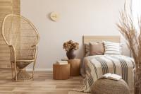 Ratanové kreslo a béžová posteľ vo svetlej spálni