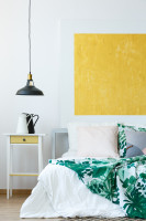 Nočný stolík vo svetlej spálni so žltým obrazom