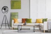 Rohová pohovka v bielej obývačke so zelenými doplnkami