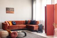 Hnedá rohová pohovka s dekoračnými vankúšmi