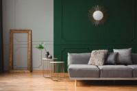 Sivá pohovka a okrúhle zrkadlo na zelenej stene