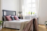 Drevená posteľ s dekoračnými vankúšmi a pletenou dekou