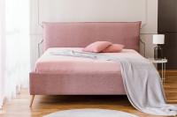 Ružová čalúnená posteľ s bielou dekoračnou dekou