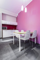 Biely jedálenský stôl a stoličky v kuchyni s ružovou stenou