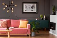 Ružová pohovka v retro obývačke so sivými stenami