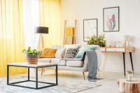 Svetlá pohovka s dekoračnými vankúšmi a konferenčný stolík s kovovou podnožou