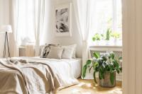 Posteľ a stojanová lampa vo vzdušnej bielej spálni