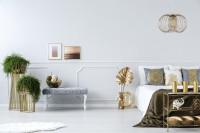 Posteľ so zlatými doplnkami v priestrannej bielej spálni