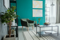 Čalúnené retro kreslo v obývačke s tyrkysovou stenou