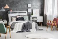 Drevená manželská posteľ a retro kreslá v priestrannej spálni