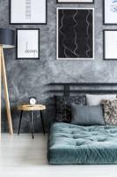 Manželská posteľ v japonskom štýle v spálni so sivou stenou
