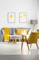 Sivá pohovka a retro kreslo so žltými dekoráciami