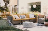Ratanová pohovka a kreslo na terase s dekoračným osvetlením