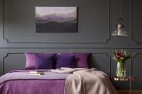 Manželská posteľ s fialovými obliečkami v sivej glamour spálni