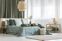 Drevená manželská posteľ v boho spálni s prírodnými doplnkami