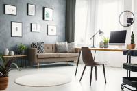 Látková pohovka s dekoračnými vankúšmi v obývačke so sivou galériovou stenou