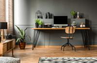 Písací stôl a industriálna stolička v pracovni so sivou stenou
