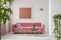 Ružová pohovka a sada okrúhlych kovových konferenčných stolíkov