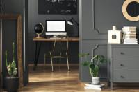 Písací stôl v elegantnej sivej pracovni so zlatými doplnkami