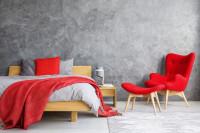 Drevená manželská posteľ a červené kreslo v sivej spálni