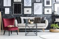 Svetlá pohovka a bordové kreslo v obývačke so sivou stenou s obrazmi